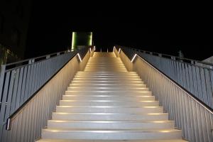 Das imposante Bauwerk bildet eines der Highlights entlang des Henne-Boulevards und wird, insbesondere durch die Handlaufbeleuchtung, von weither wahrgenommen. Die Konstruktion der Treppe setzt sich durch ihre rustikale Stahloptik bewusst von der grünen Flanke des Damms ab und bildet einen spannenden Baustein innerhalb des Landschaftsraums am nördlichen Hennesee.